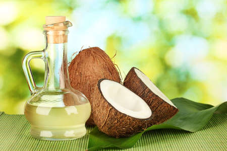 decanter with coconut oil and coconuts on green background photo