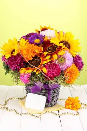 Beautiful bouquet of bright flowers with paper note on wooden table on green background photo