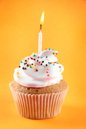cake with icing: tasty birthday cupcake with candle, on orange background
