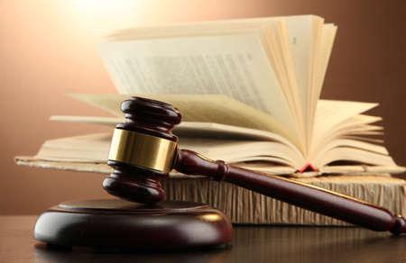 giustizia: martelletto di legno e libri sul tavolo in legno, su sfondo marrone