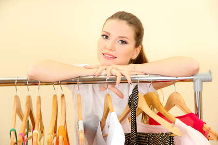 beautiful young woman near rack with hangers photo