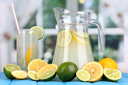 Citrus lemonade in pitcher and glass of citrus around on blue wooden table on window background Stock Photo - 15537959