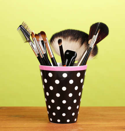 Makeup brushes in a black polka-dot cup on yellow background photo