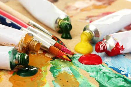 Abstrait acrylique tubes de peinture de peinture et les pinceaux sur palette en bois Banque d'images