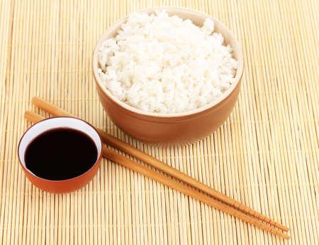 Bowl of rice and chopsticks on bamboo mat photo