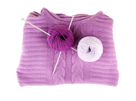 Purple sweater and a ball of wool isolated on white photo
