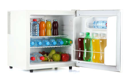 frig: mini fridge full of bottles of juice, soda and fruit isolated on white