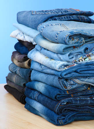 Many jeans stacked in a piles on blue background photo
