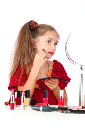 nail polish bottle: little girl in her mothers dress, is trying painting her face Stock Photo