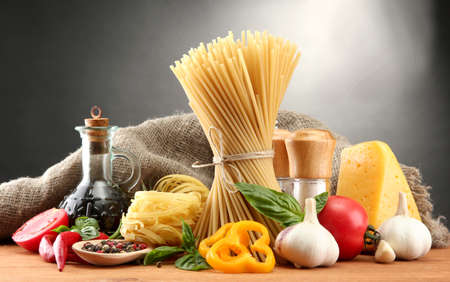 Pasta spaghetti, vegetables and spices, on wooden table, on grey background Stock Photo - 15602400