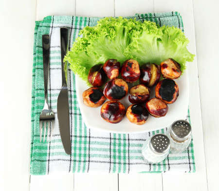roasted chestnuts with lettuce in the plate on white wooden background photo