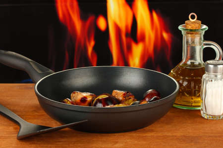 roasted chestnuts in the pan and decanter with oil, salt and pepper on wooden table close-up photo