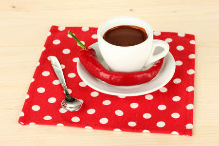 white cup with hot chocolate and chili pepper on wooden background photo