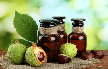 medicine bottles with chestnuts and leaves, on green background photo