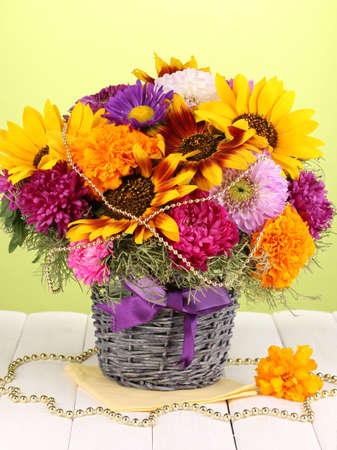 ronantic: Beautiful bouquet of bright flowers on wooden table on green background Stock Photo