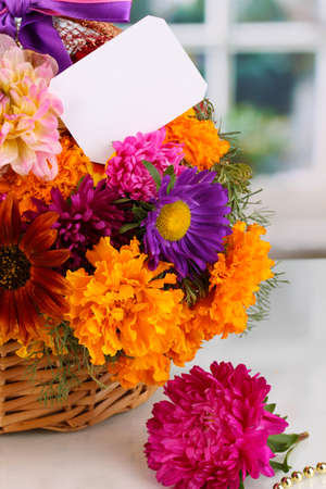 Beautiful bouquet of bright flowers in basket with paper note close-up on white table on window background