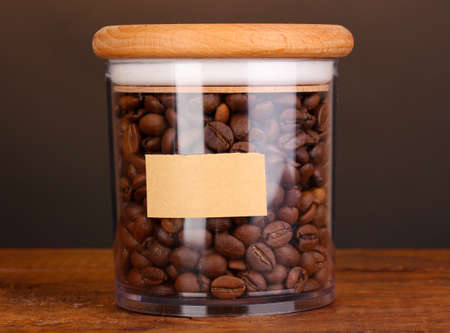 Coffee beans in jar on table on brown background photo