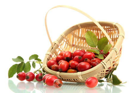 ripe hip roses with leaves in basket, isolated on white photo