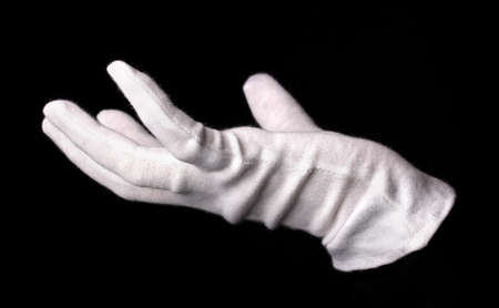 Hand in white glove making sign isolated on black Stock Photo - 15591960