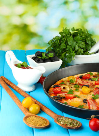 colorful composition of delicious pizza, vegetables and spices on blue wooden background close-up Stock Photo - 15593114