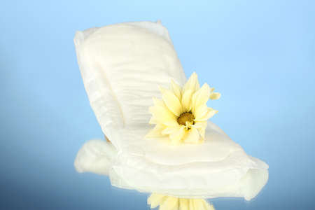 Panty liner and yellow flower on blue background close-up Stock Photo - 15592162