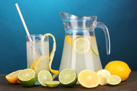 Citrus lemonade in pitcher and glass of citrus around on wooden table on blue background Stock Photo - 15609427