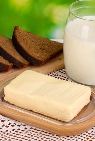 Butter on wooden holder surrounded by bread and milk on natural background close-up Stock Photo - 15609425