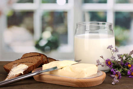 Butter on wooden holder surrounded by bread and milk on wooden table on window background Stock Photo - 15609441