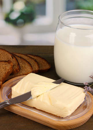 Butter on wooden holder surrounded by bread and milk on wooden table on window background Stock Photo - 15609361