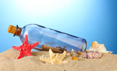 castaway: Glass bottle with note inside on sand, on blue background