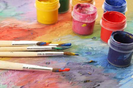 pintor: paleta de madera del arte con la pintura y los pinceles, primer plano
