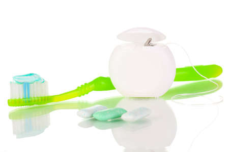 Toothbrush, chewing gum and dental floss isolated on white photo