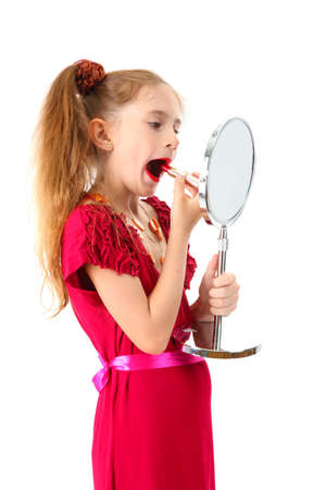 little girl in her mother's dress, is trying painting her lips, isolated on white Stock Photo - 15736423