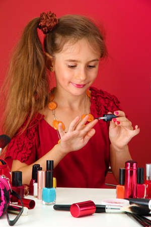 little girl in her mother's dress, is trying painting her nails photo
