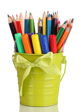 Colorful pencils and felt-tip pens in green pail isolated on white photo