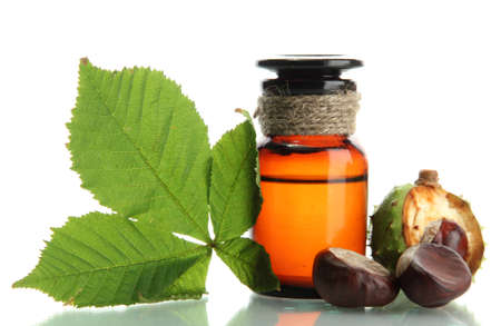 medicine bottle with chestnuts and leaves, isolated on white photo