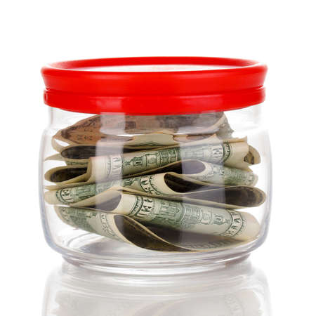 saving tips: Clear glass jar for tips with money isolated on white Stock Photo