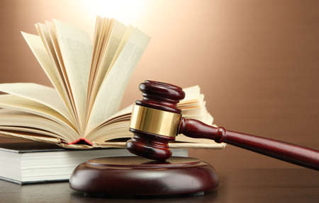abogado: Mazo de madera y libros sobre la mesa de madera, sobre fondo marr�n