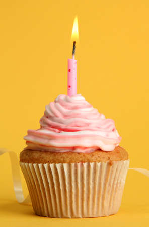 birthday cupcakes: tasty birthday cupcake with candle, on yellow background