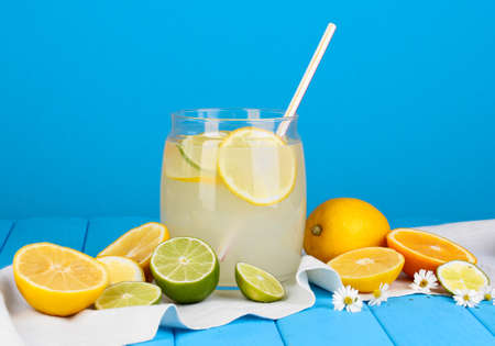 Citrus lemonade in glass bank of citrus around on wooden table on blue background Stock Photo - 15616729