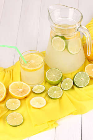 Citrus lemonade in glass and pitcher of citrus around on yellow fabric on white wooden table close-up Stock Photo - 15642274
