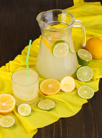 Citrus lemonade in glass and pitcher of citrus around on yellow fabric on wooden table close-up Stock Photo - 15642348