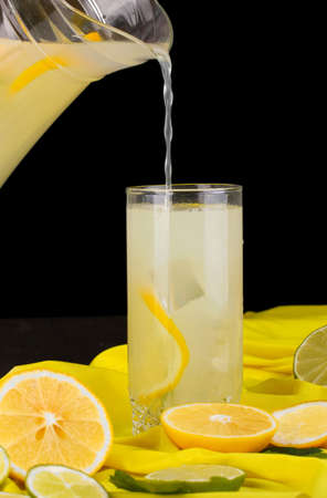 Citrus lemonade in glass and pitcher of citrus around on yellow fabric on wooden table close-up Stock Photo - 15616377