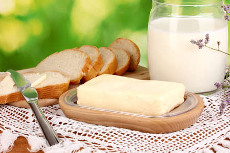 Butter on wooden holder surrounded by bread and milk on natural background photo