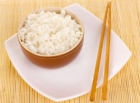Bowl of rice and chopsticks on plate on bamboo mat photo