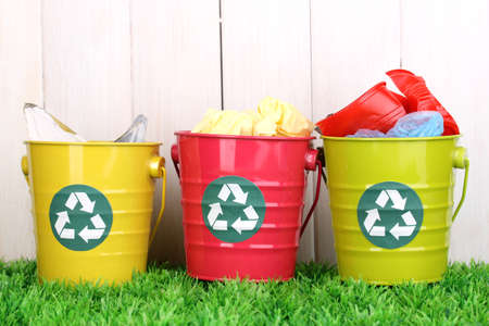 environmental protection: Recycling bins on green grass near wooden fence Stock Photo
