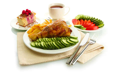 Roast chicken cutlet with boiled potatoes and  vegetables, cup of tea and dessert, isolated on white photo