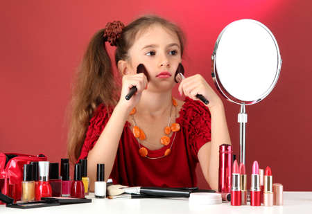 little girl in her mother's dress with make up brushes Stock Photo - 15736415
