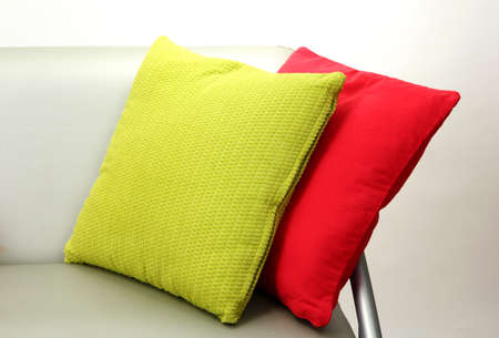 Colorful pillows on couch isolated on white photo