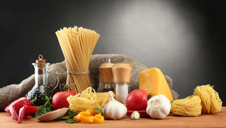 Pasta spaghetti, vegetables and spices, on wooden table, on grey background Stock Photo - 15684292